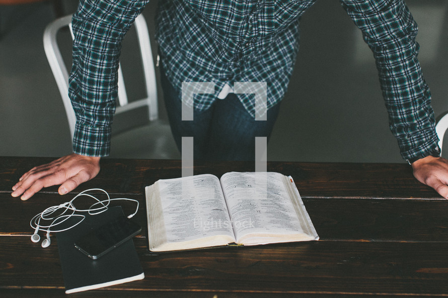 man resting his hands on a table reading a Bible