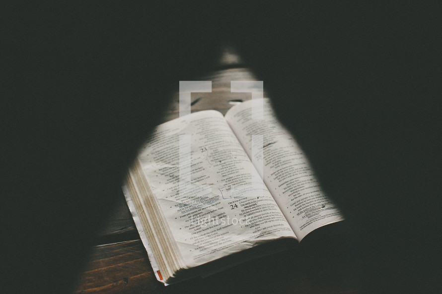 half opened shutter shot of a Bible on a wood table