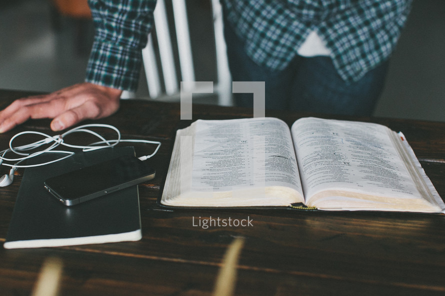 Man's hand leaning on wooden desk with iPod reading open Bible.