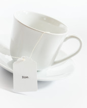 tea cup with the word rise on the tea bag