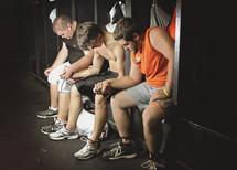 Three men holding hands praying in a locker room