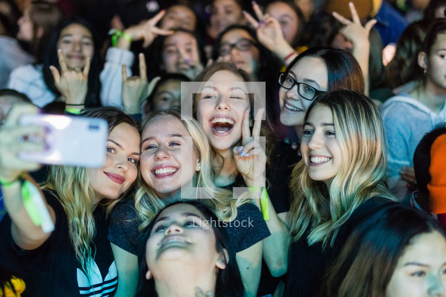 teen girls taking a selfie in the crowd at a youth conference