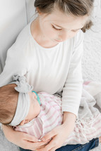 a big sister holding her infant little sister
