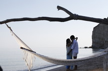 a hammock on a beach and a couple hugging