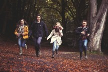 youth running outdoors through fall leaves