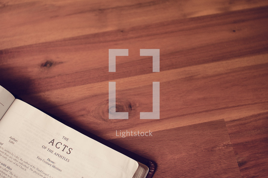 BIble on a wood floor opened to Acts