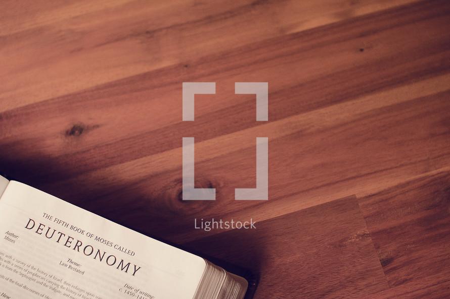 BIble on a wood floor opened to Deuteronomy