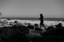 woman walking onto a rocky beach