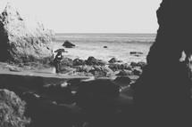 woman walking on a rocky beach