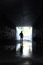 a man walking through a dark wet tunnel