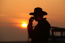silhouette of a cowboy on a cellphone at sunset