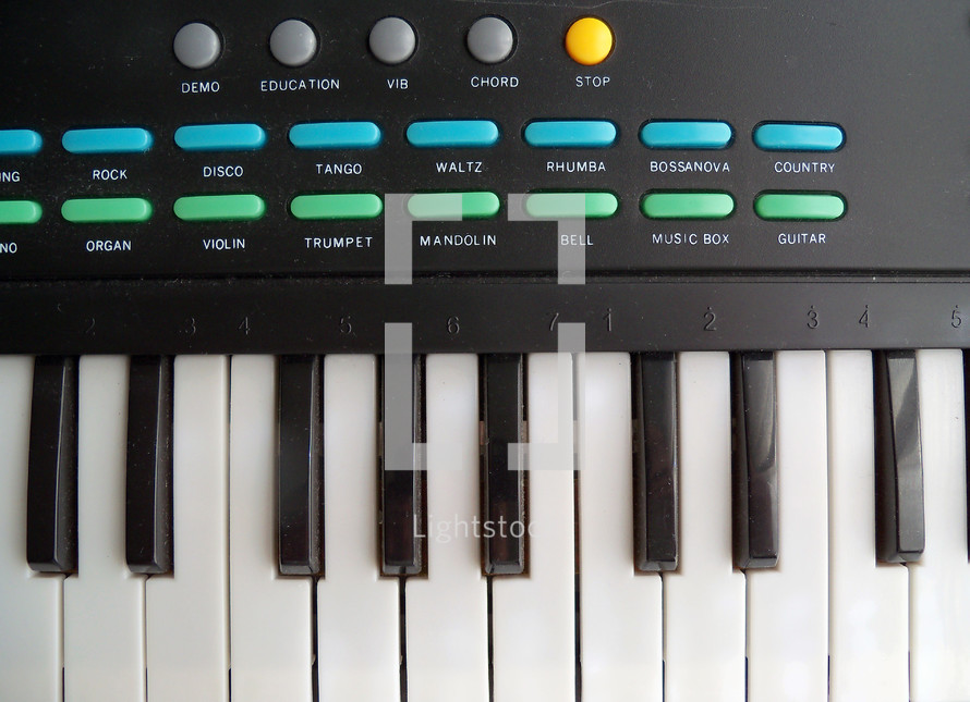 Upclose view of an electronic keyboard with piano keys, programmable buttons for different styles of music and synthesized sounds to emulate for a concert or recording session for praise, worship and contemporary Christian music bands on tour or recording live in a recording studio.