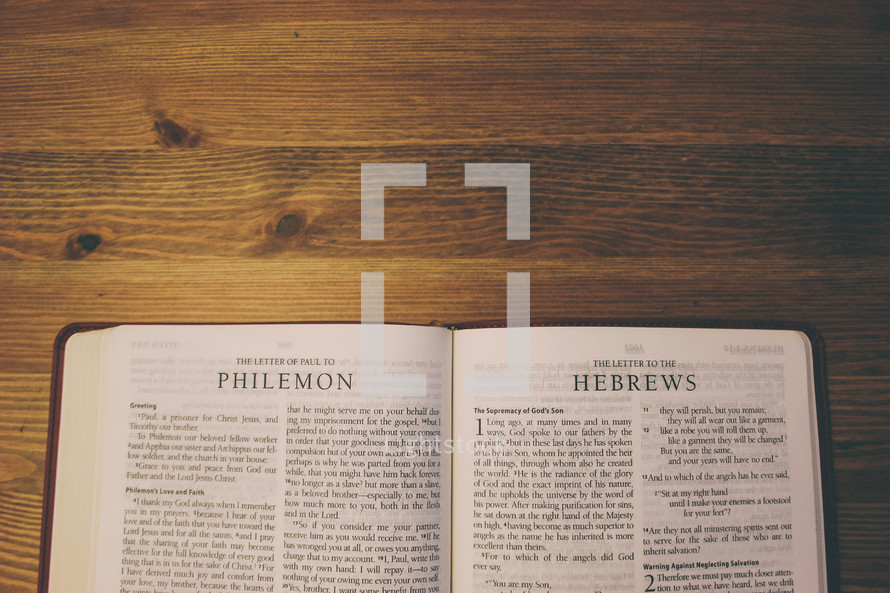 Bible on a wooden table open to the Letter of Paul to Philemon and the Letter to the Hebrews.
