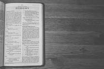 Bible on a wooden table open to the Letter to the Hebrews.