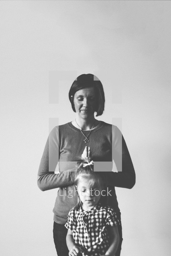 Woman praying over a child.