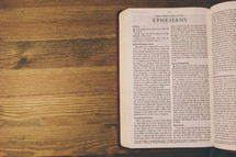 Bible on a wooden table open to the book of Ephesians.