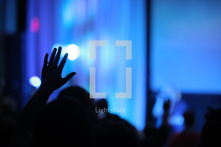 silhouette of a raised hand at a worship service