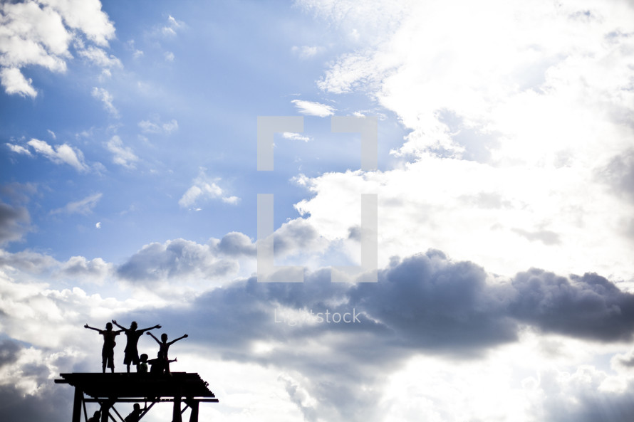 children on a roof with arms raised in worship to God