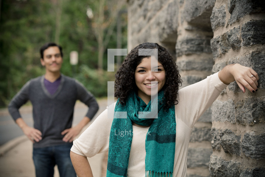 Smiling woman leaning on stone wall with smiling man standing with hands on his hips in the background.
