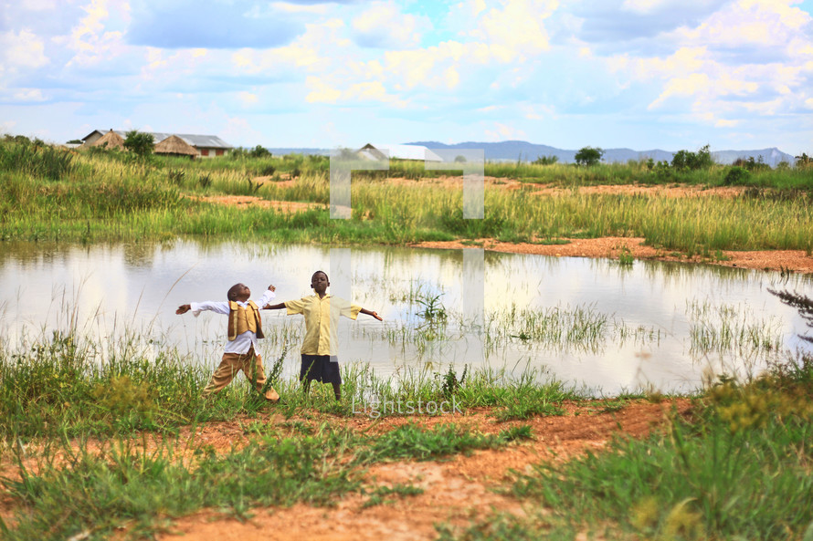 Boys with arms spread standing on the edge of a pond by a village, looking toward the sky.