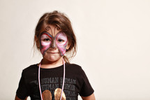 little girl with her face painted as a butterfly