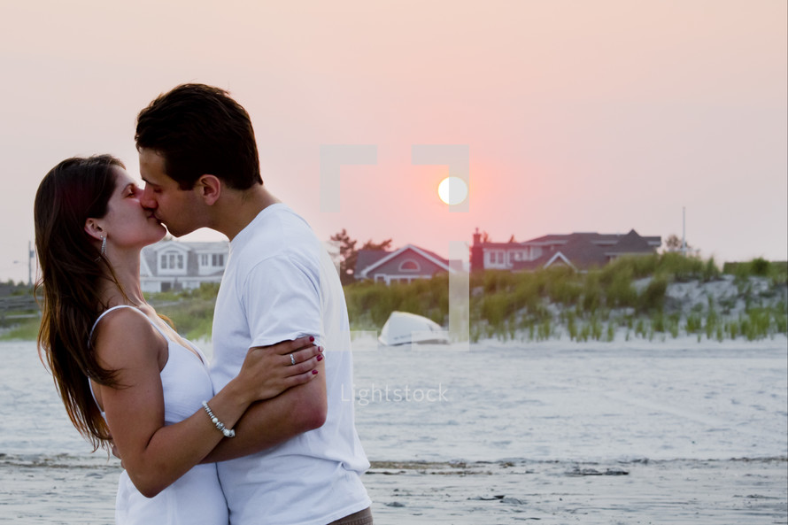 A man and woman kissing on a beach.