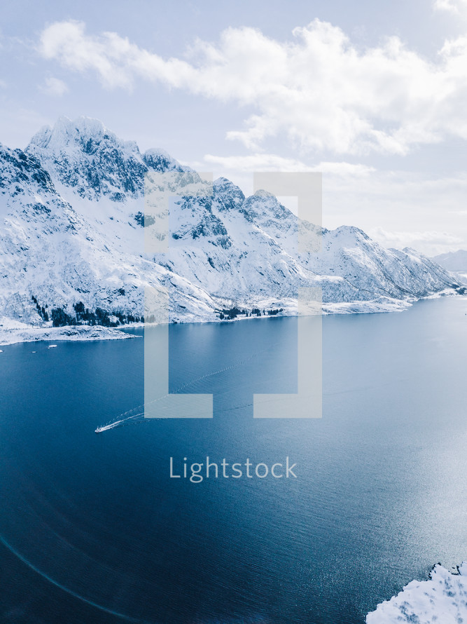 jagged mountains with snow and ocean view