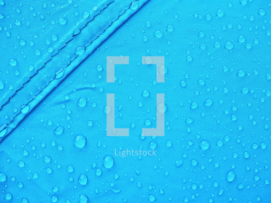 Blue rainproof tent sheet with morning rain drops