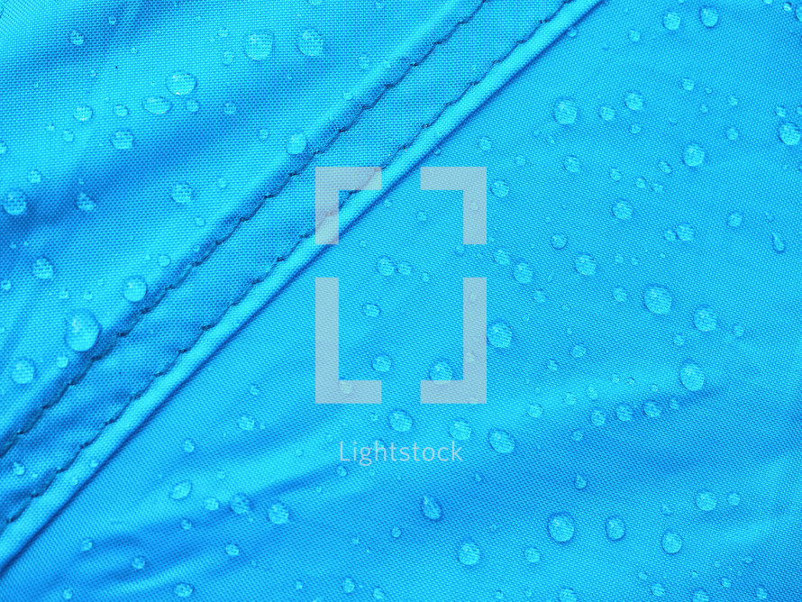 Blue rainproof tent sheet with morning rain drops