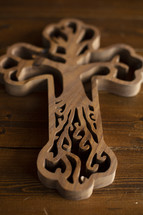 wooden cross with tree carving detail on a wood background