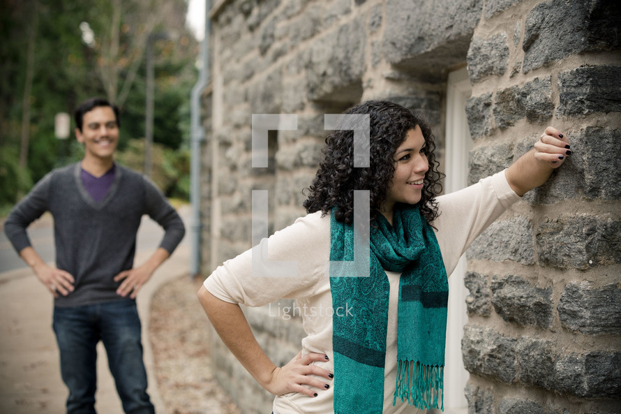 Woman leaning against stone wall with smiling man standing with hands on hips in the background.