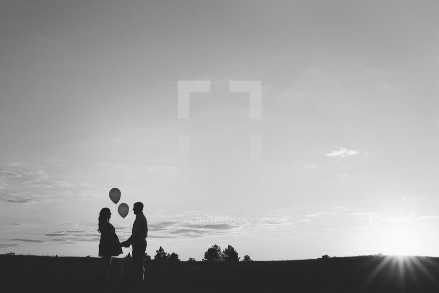 silhouettes of pregnant wife holding hands with her husband while holding balloons