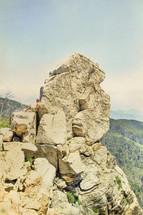 man resting on a rocky peak