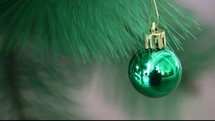green Christmas ornament handing on a Christmas tree