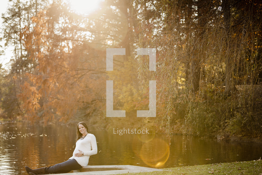 pregnant woman sitting in front of a lake with her hands on her pregnant belly