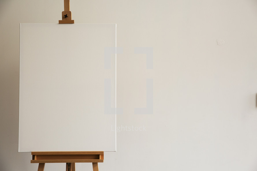 A blank canvas on a painter's easel.