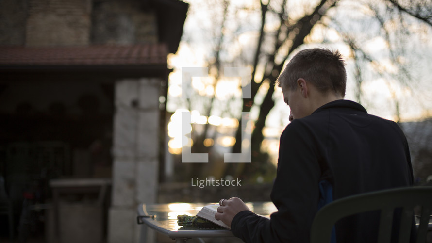 a man reading a Bible outdoors at a table