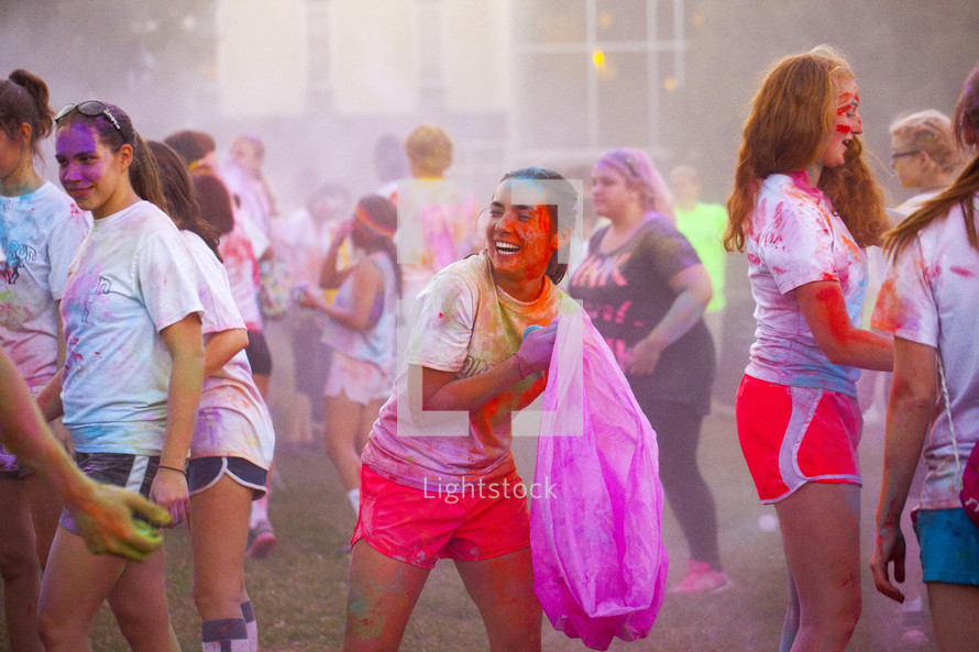 teens tossing color packets at a color run