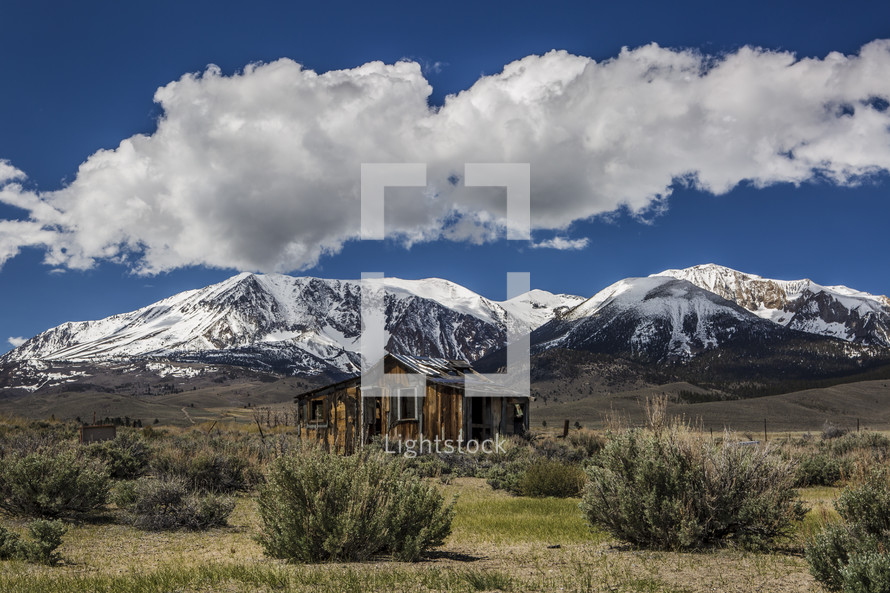 snow on mountains behind a cabin