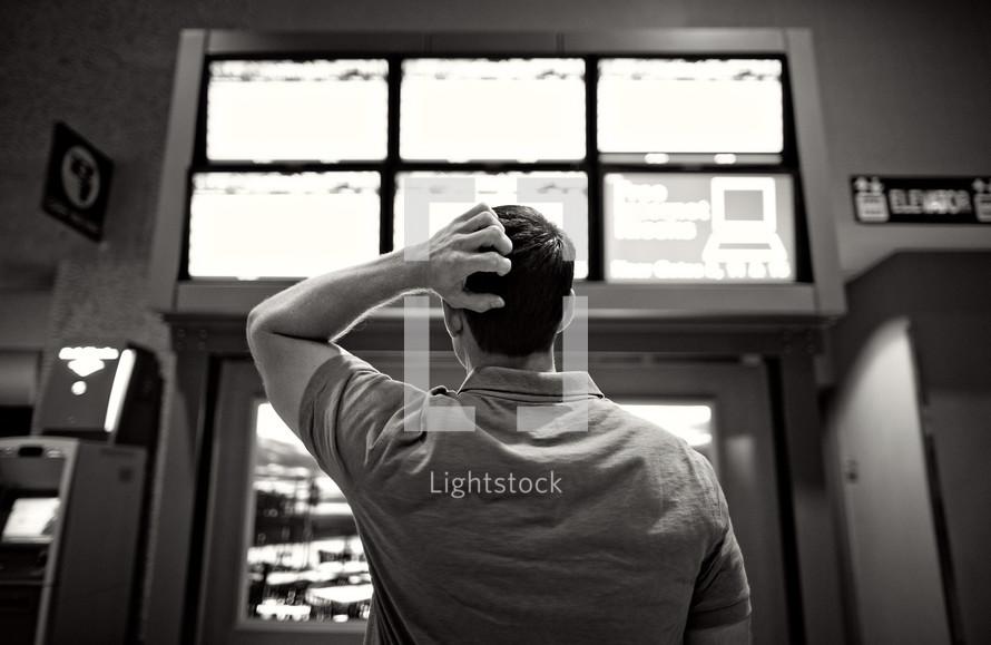 man standing scratching his head