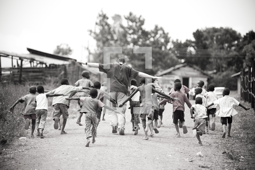 Man running with children on a dirt road