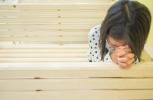 praying child on a bench