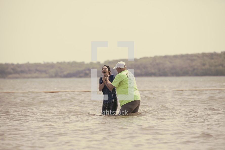 baptism of a woman in lake water