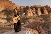 Woman with a guitar standing on a canyon ridge.