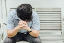 a man praying on a bench