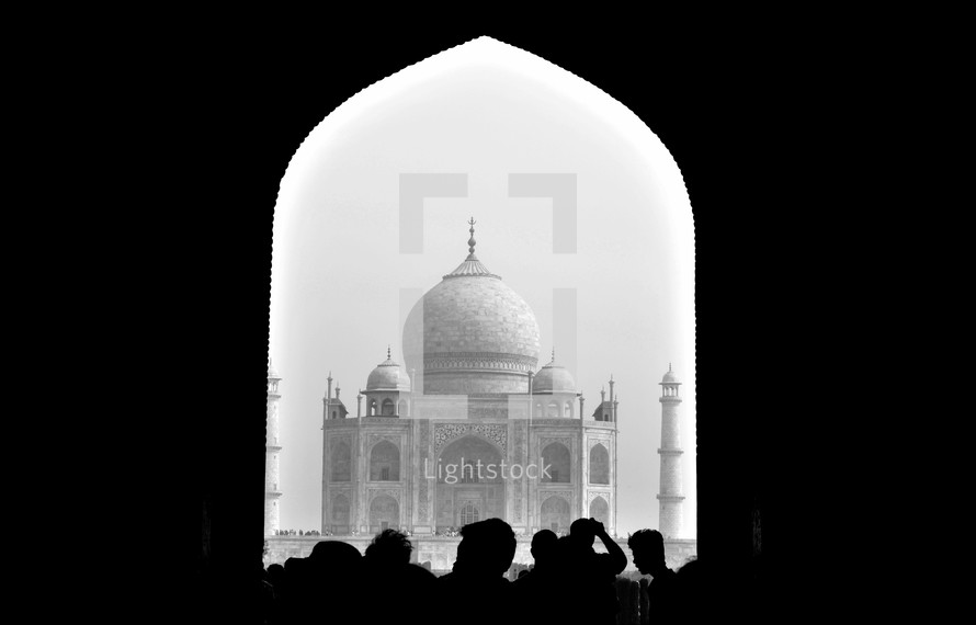 silhouettes of tourists in front of the Taj Mahal