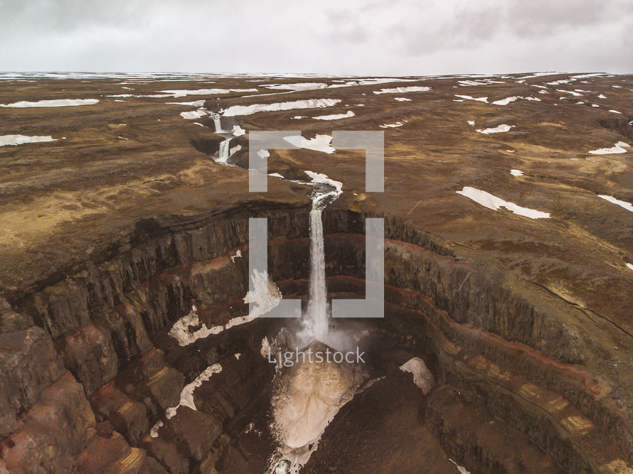 aerial view over a waterfall flowing over brown cliffs