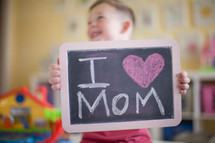 a little boy holding a chalkboard sign that reads I heart mom
