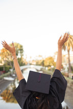 female African American graduate with raised hands