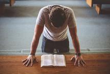 a man kneeling at an altar reading a Bible